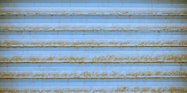 Zardzewiała metalowa powierzchnia żaluzji, niebieski metaliczny żebrowany płot, faktura prążkowanej ściany. tła miejskiego grunge z liniami prostymi. element zewnętrzny