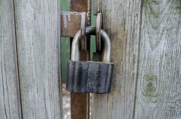 Zardzewiała stara kłódka wisząca na drewnianych drzwiach stodoły, żelazna kłódka