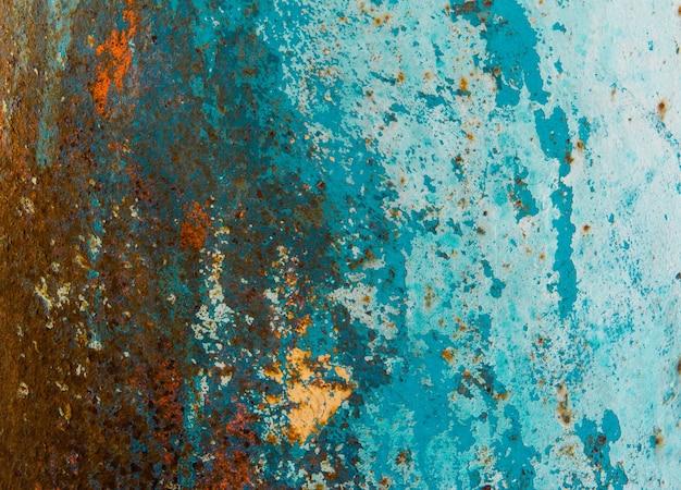 Zardzewiała tekstura materiału w kolorach pomarańczowym, zielonym i niebieskim. tło
