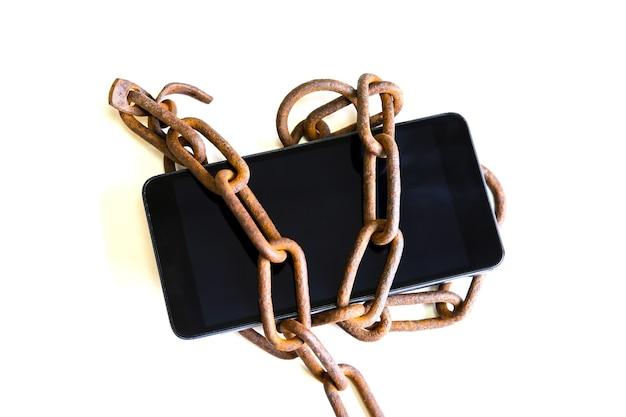 Zardzewiałe łańcuchy wokół smartfona. na białym tle. uzależniony od nowoczesnych technologii.