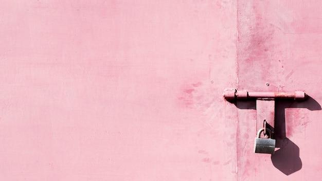 Zardzewiałe, metalicznie różowe drzwi z klawiaturą