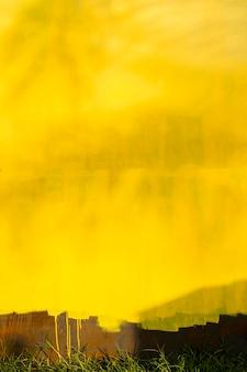 Zardzewiałe metalowe ściany tła i żółta stara farba