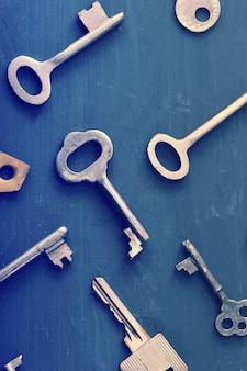 Zardzewiałe stare klucze zamyka się na ciemnej drewnianej rustykalnej powierzchni