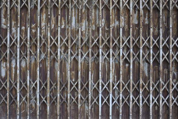 Zardzewiałe stare żelazne drzwi opuszczonego domu i pogarszają się.