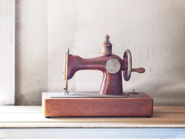 Zardzewiały stary maszyna do szycia na drewnianym stole w pokoju vintage