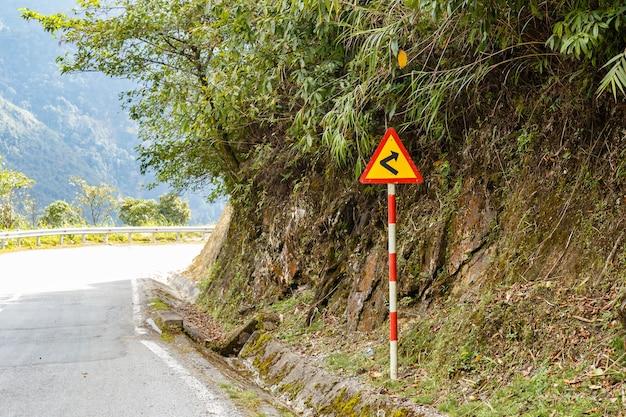 Zarejestruj niebezpieczny zakręt na górskiej drodze, wietnam, znak drogowy.