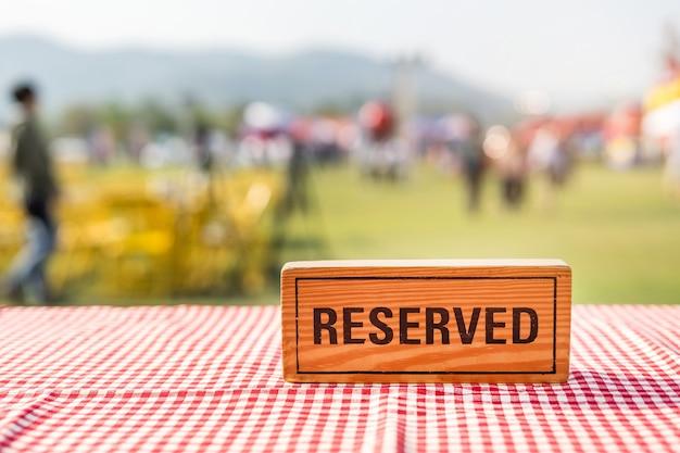 Zarezerwowany drewniany znak na plenerowym stole w wydarzeniu