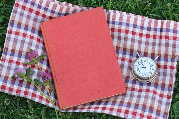 Zarezerwuj z pustą okładką na trawie, widok z góry. czytanie na świeżym powietrzu, letnie wakacje.