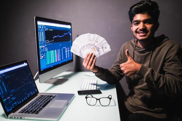 Zarób pieniądze online. anielski bogaty biznesmen z nimbem na głowie wskazującym banknotami dolarowymi, zachęcający do zarabiania w internecie, siedzący przy laptopie w miejscu pracy. kryty studio strzał na białym tle