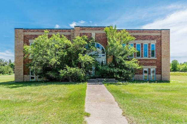Zarośnięte rośliny pokrywające wejście do opuszczonej szkoły ponteix w ponteix, saskatchewan, kanada