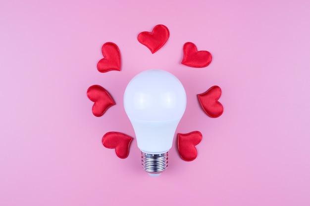Żarówka i czerwone serca na różowym tle. koncepcja walentynki