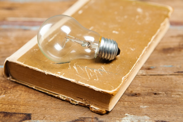 Żarówka i książka na stole. nowe pomysły