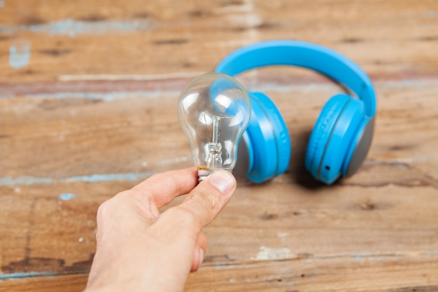 Żarówka i słuchawki na drewnianym stole