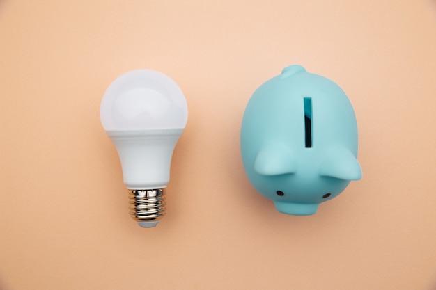 Żarówka led i niebieska skarbonka. koncepcja oszczędności energii