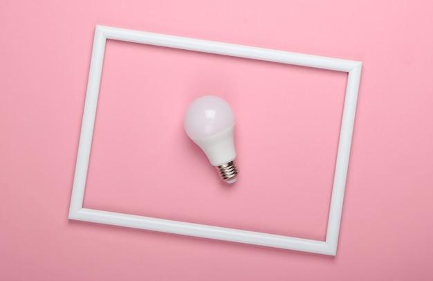 Żarówka led na różowej powierzchni z białą ramką