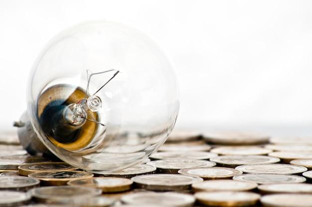 Żarówka leży na monetach euro