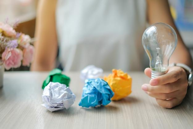 Żarówka lub lampa z kolorowym zmiętym papierem na drewnianym stole