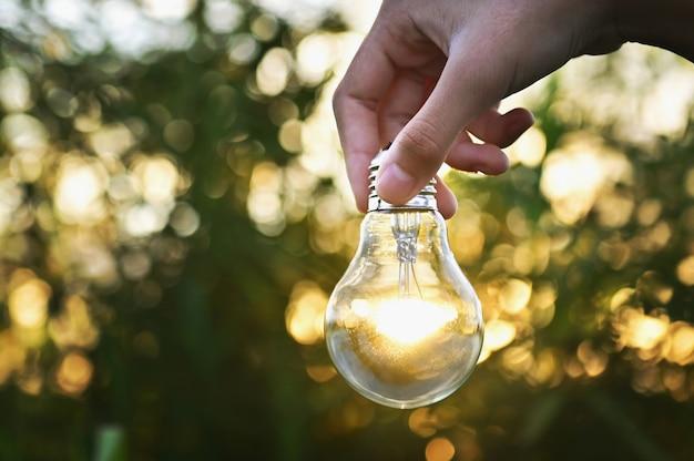 Żarówka świeci pod ręką na zewnątrz