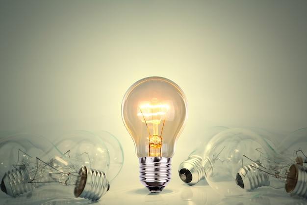 Żarówka świeci pomiędzy wieloma światłami