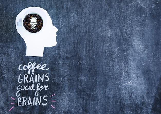 Żarówka wewnątrz ziaren kawy kubek nad białą papierową wycinanki głową na blackboard z tekstem