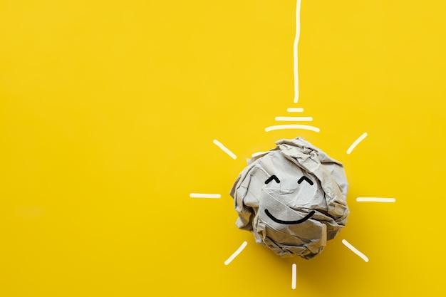 Żarówka z papieru z recyklingu z uśmiechniętą twarzą na żółtym tle