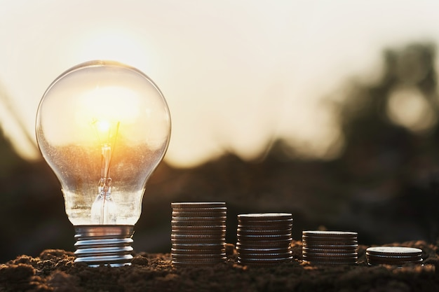 Żarówka z stos monet na ziemi. oszczędzanie na rachunkowości pieniężnej. koncepcja energii mocy
