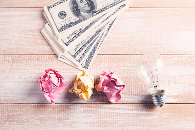 Żarówka, zmięte papiery i pieniądze