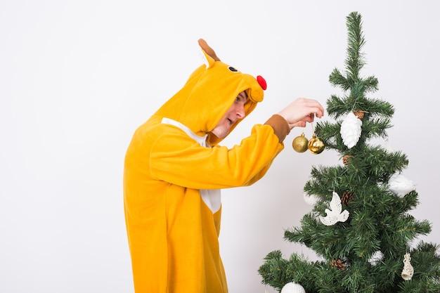 Żart, boże narodzenie, koncepcja ludzi - mężczyzna w stroju jelenia dekorowanie choinki na białym tle.