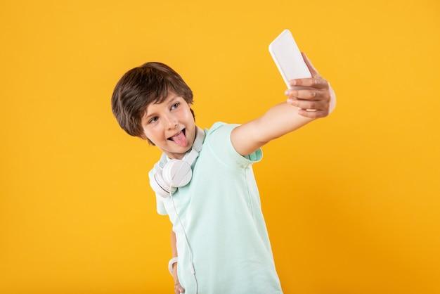 Żartować. zaalarmowany szczupły chłopiec w słuchawkach i robienie selfie