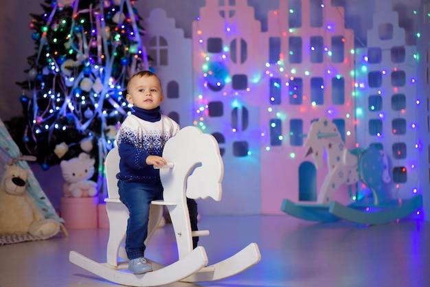 Żartuje chłopiec bawić się z zabawkami w domu, salowy. kolorowe lampki świąteczne. pojęcie rodziny, wakacje, styl życia.