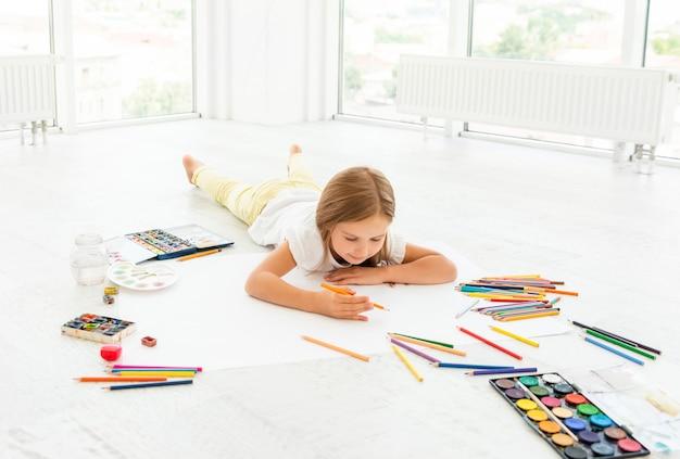 Żartuje dziewczyny na podłogowym rysunku z ołówkami