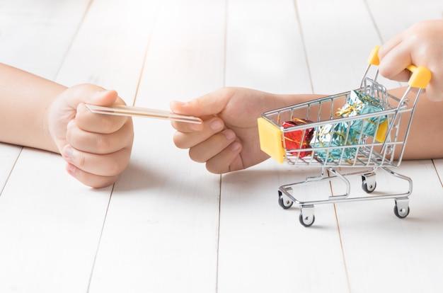 Żartuje ręki trzyma kredytową kartę i wózek na zakupy na białym drewnianym tle. koncepcja zakupów online