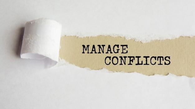 Zarządzaj konfliktami. słowa. tekst na szarym papierze na tle rozdarty papier.