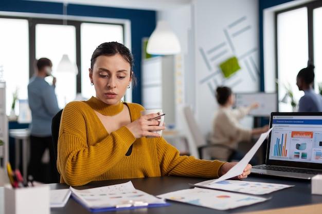 Zarządzający firmą finansową czytający analizujące statystyki w miejscu pracy wykonawczy przedsiębiorca, lider menedżera siedzący przy projektach z różnorodnymi kolegami.
