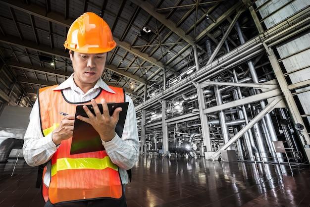 Zarządzający inżynier w akcie notatek w celu sprawdzenia systemu rur elektrowni