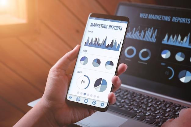 Zarządzanie marketingowe i raporty. zakończenie tylni widok osoba trzyma smartphone i patrzeje z raportami marketingowymi na ekranie telefonu komórkowego i laptopu i patrzeje.