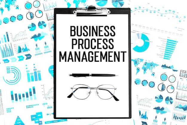 Zarządzanie procesami biznesowymi tekst w schowku, długopis, okulary, wykresy. leżał płasko.