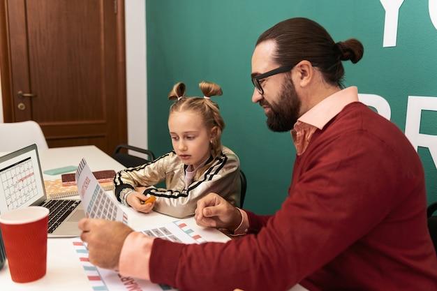 Zasady czytania urocza jasnowłosa dziewczyna nosząca bransoletki na dłoni, która uważnie czyta nowe słowa