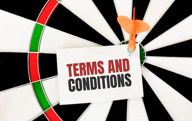 Zasady i warunki pismo odręczne na papierze ze strzałką do darta i tarczą do rzutek.