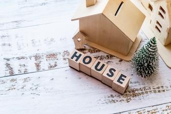 Zasięrzutny widok domu model z domowymi drewnianymi blokami i choinką na białej textured powierzchni