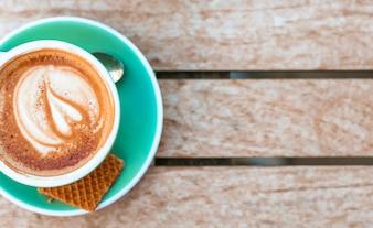 Zasięrzutny widok filiżanka z kierową latte sztuką na drewnianym stole