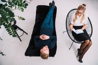 Zasięrzutny widok młody żeński psycholog konsultuje młodego człowieka podczas psychologicznej terapii sesi