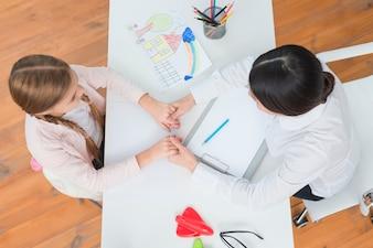 Zasięrzutny widok mała dziewczynka i żeński psycholog trzyma each inny rękę na bielu stole