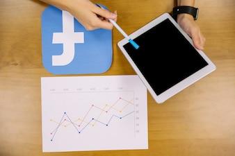 Zasięrzutny widok osoba trzyma cyfrową pastylkę analizuje facebook wykres