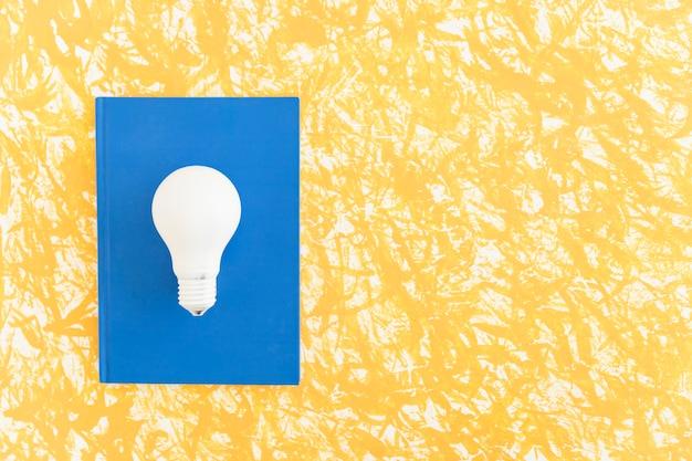 Zasięrzutny widok białe światło żarówka na błękitnym notatniku nad deseniowym tłem