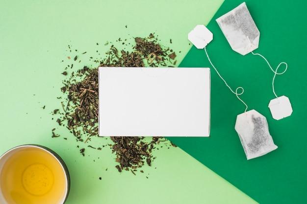 Zasięrzutny widok biały pudełko z herbacianą filiżanką i herbacianymi torbami na zielonym tle