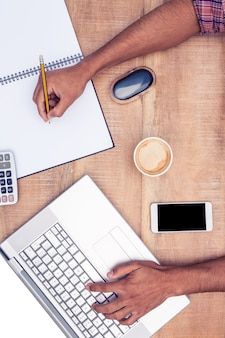 Zasięrzutny widok biznesmen pracuje na laptopie podczas gdy pisać na książce przy biurkiem w biurze