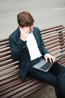 Zasięrzutny widok biznesmena obsiadanie na ławce przy ulicą używać laptop