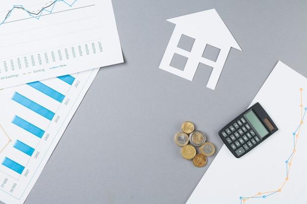Zasięrzutny widok biznesowy biurko z brogować monetami; kalkulator; wycinanka i wykres domu