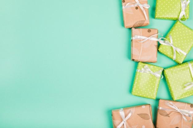 Zasięrzutny widok brown i zielony papier zawijający prezentów pudełka na zielonym tle
